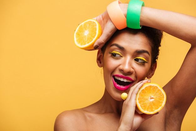 Portrait de femme afro-américaine souriante avec un maquillage élégant tenant deux moitiés d'orange juteuse dans les deux mains isolées, sur un mur jaune