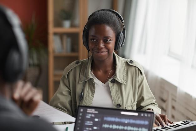 Portrait de femme afro-américaine souriante portant des écouteurs tout en composant de la musique en studio d'enregistrement