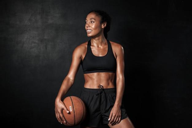 Portrait d'une femme afro-américaine souriante en tenue de sport tenant un basket-ball isolé sur fond noir