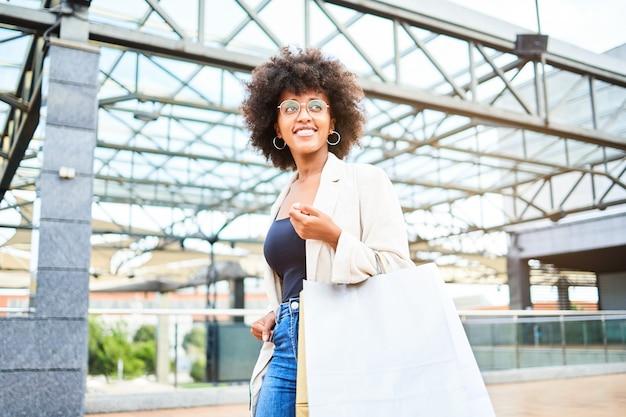 Portrait d'une femme afro avec des sacs shopping dans un centre commercial