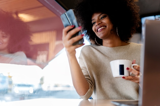 Portrait d'une femme afro séduisante utilisant un téléphone portable au café. concept de femme d'affaires