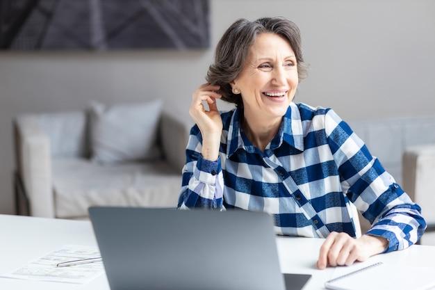 Portrait d'une femme d'âge d'affaires heureuse avec un ordinateur portable assis à un bureau dans un bureau ou à la maison regarde loin de la fenêtre et sourit