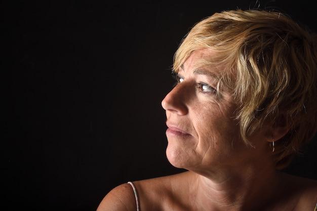 Portrait d'une femme d'âge moyen sur fond noir