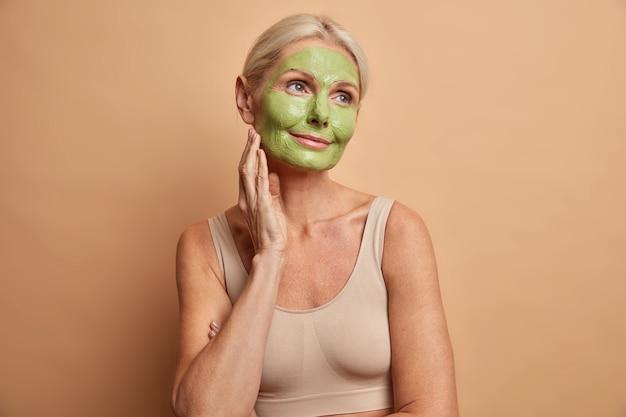 Portrait de femme d'âge moyen rêveur applique un masque vert sur le visage se dresse pensivement et regarde ailleurs subit des procédures de beauté habillé avec désinvolture isolé sur mur beige