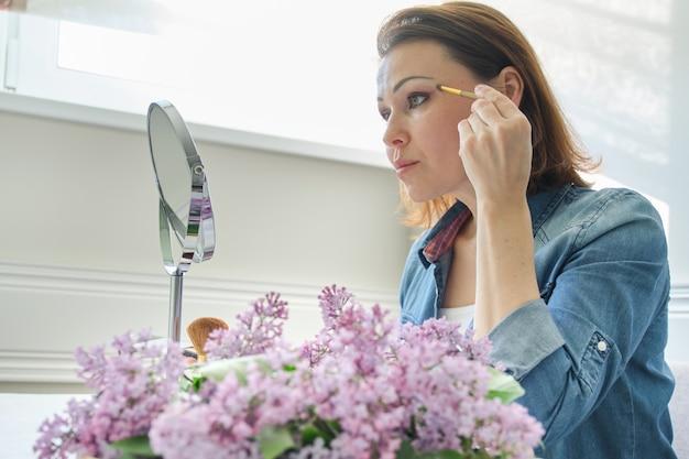 Portrait d'une femme d'âge mûr avec miroir de maquillage