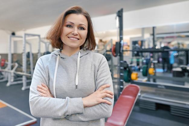 Portrait de femme d'âge mûr souriante dans une salle de sport