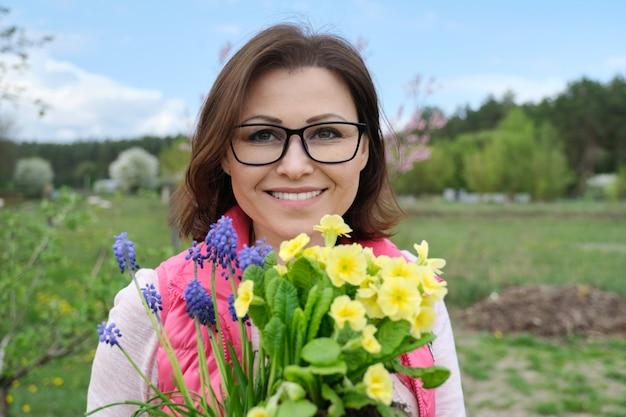 Portrait de femme d'âge mûr souriante avec des fleurs