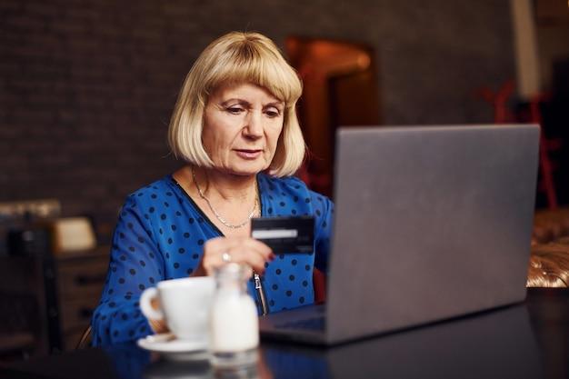 Portrait d'une femme âgée assise à l'intérieur du café avec un ordinateur portable moderne et une carte de crédit en main.