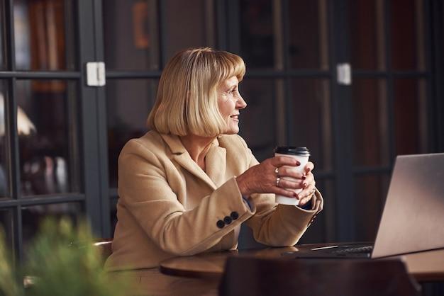 Portrait d'une femme âgée assise à l'intérieur du café avec un ordinateur portable moderne et une tasse de boisson dans les mains.