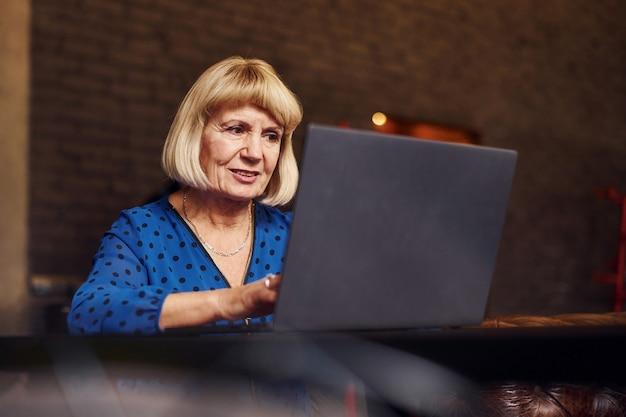 Portrait d'une femme âgée assise à l'intérieur du café avec un ordinateur portable moderne.