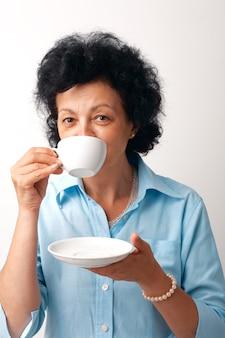 Portrait d'une femme âgée de boire dans une tasse et holdig une soucoupe