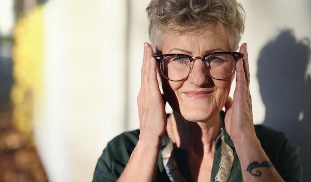 Portrait de femme âgée debout à l'extérieur de la ville, regardant la caméra.