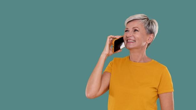 Portrait d'une femme âgée élégante parlant au téléphone