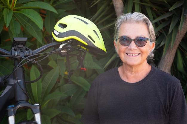 Portrait d'une femme âgée heureuse assise en plein air près de son vélo électrique. mode de vie sain, bien manger et faire du mouvement. fond de jardin riche de plantes tropicales vertes