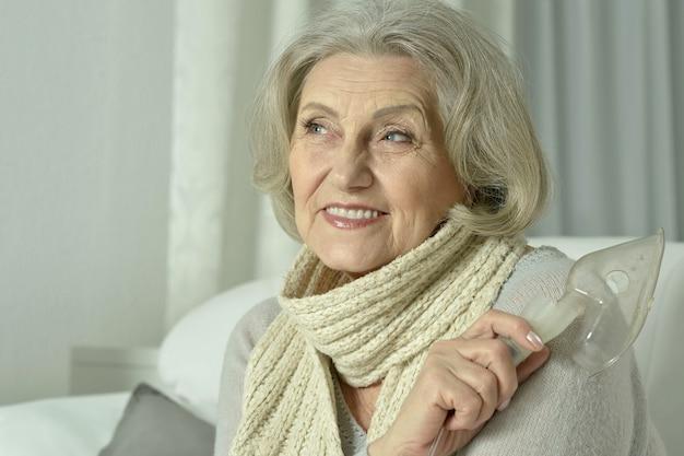 Portrait de femme âgée avec inhalation de grippe