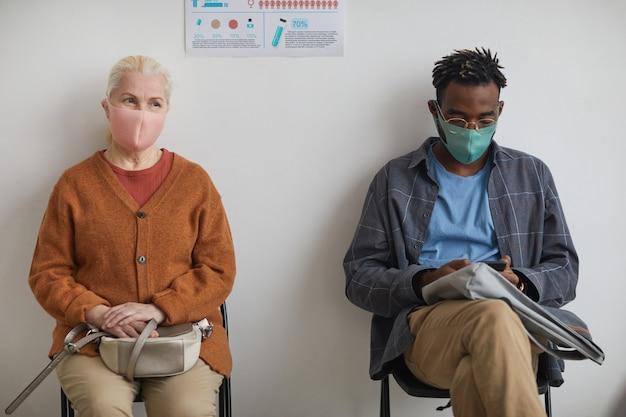 Portrait d'une femme âgée et d'un jeune homme afro-américain faisant la queue à la clinique ou au centre de vaccination portant tous deux des masques