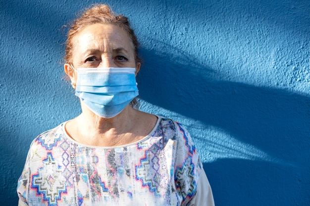 Portrait d'une femme âgée portant un masque facial à côté d'un mur bleu.