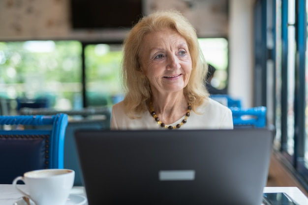 Portrait de femme âgée senior assis et à l'aide d'un ordinateur portable