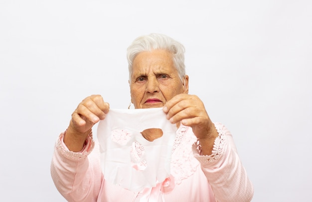 Portrait d'une femme âgée en serviette de bain enlevant un masque facial en coton rajeunissant sur fond de studio clair. belle dame mature utilisant un produit cosmétique anti-âge comment utiliser un masque cosmétique