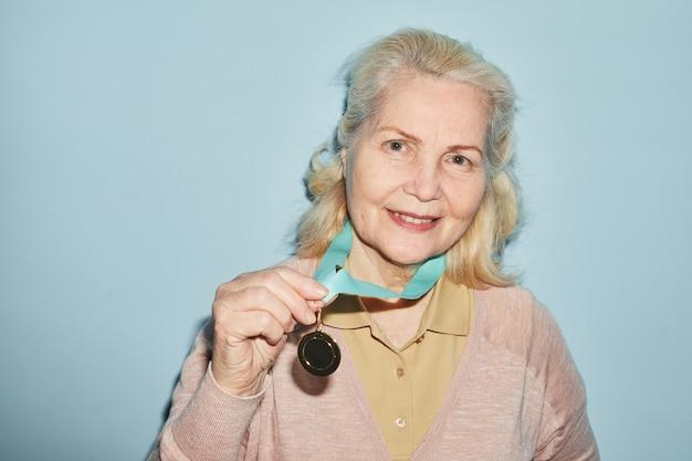 Portrait d'une femme âgée souriante portant une médaille et regardant la caméra en se tenant debout sur fond bleu, espace pour copie