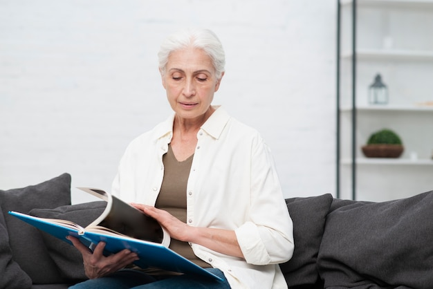 Portrait de femme âgée tenant un magazine