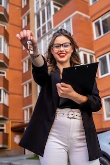 Portrait d'une femme agent immobilier debout devant une nouvelle maison. concept de vente ou de location