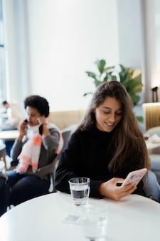 Portrait de femme à l'aide de smartphone alors qu'il était assis dans un café