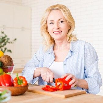 Portrait, femme aînée, couper, les, poivron rouge, à, couteau, couper planche