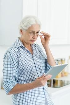 Portrait, femme aînée, debout, cuisine, regarder, tablette numérique