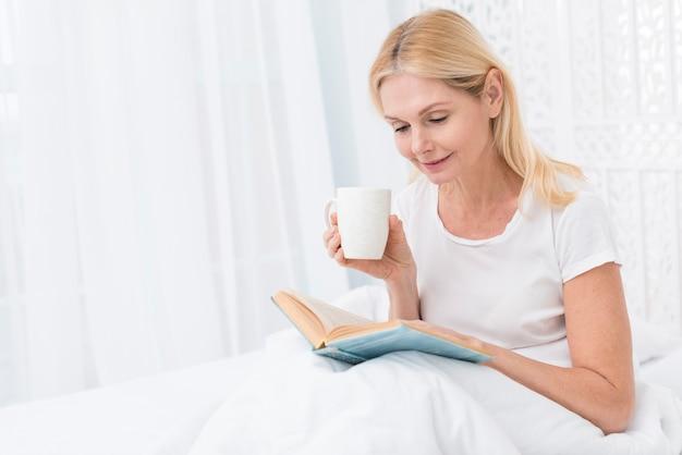 Portrait, de, femme aînée, lecture livre, dans lit