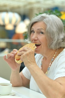 Portrait, de, a, femme aînée, manger, hamburger