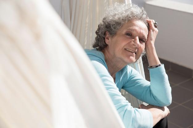 Portrait, de, femme aînée, sourire, mensonge hamac, sur, balcon