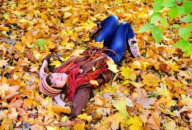 Portrait de femme allongée sur les feuilles d'automne dans le parc.