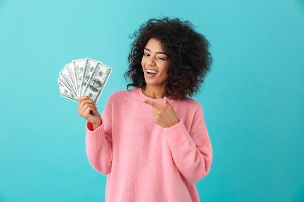 Portrait de femme américaine des années 20 avec une coiffure afro tenant beaucoup de billets en dollars d'argent, isolé sur mur bleu