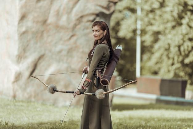 Portrait de femme avec arc et flèche sur fond flou