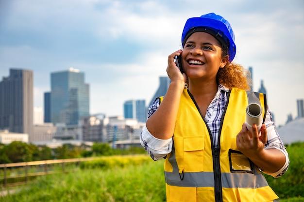 Portrait de femme architecte debout avec des dessins de construction en rouleau de papier et de communication via les smartphones.