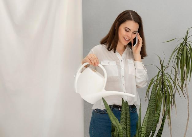Portrait femme arrosage des plantes tout en parlant sur mobile