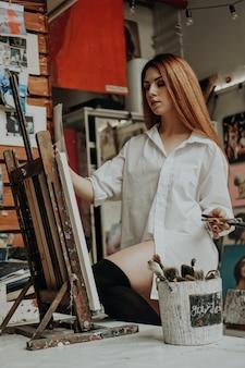 Portrait de femme artiste avec pinceau en atelier d'art