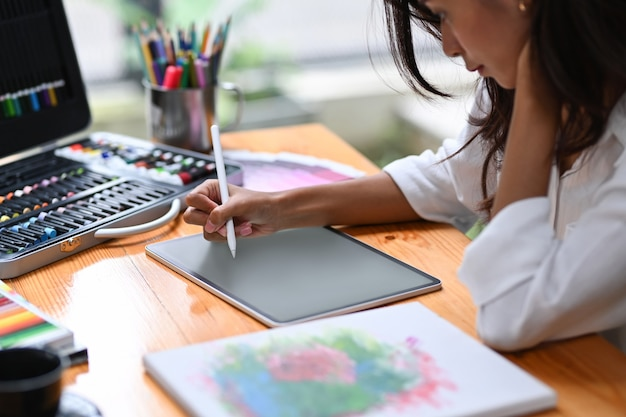 Portrait d'une femme artiste travaillant avec une tablette numérique dans son atelier.