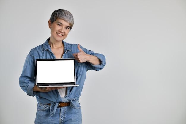 Portrait d'une femme asiatique d'âge moyen des années 50 vêtue d'une chemise en jean décontractée t-shirt blanc tenant un ordinateur portable avec écran d'espace de copie vierge et thump up isolé sur fond blanc. regarder la caméra