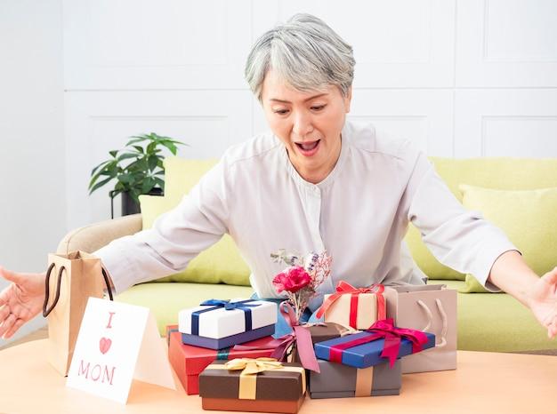 Portrait d'une femme asiatique âgée recevant des coffrets cadeaux et souriant à la maison
