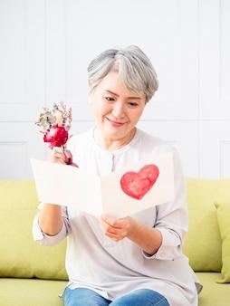 Portrait d'une femme asiatique âgée reçoit une carte et des fleurs