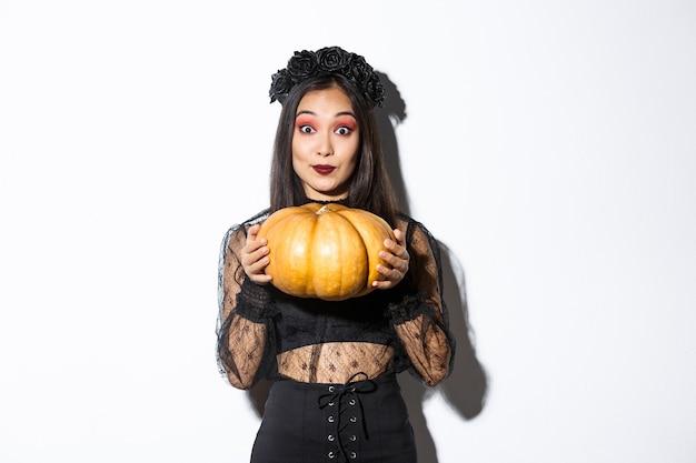 Portrait de femme asiatique assez excitée en costume d'halloween, déguisée en sorcière ou veuve et tenant la citrouille, debout sur fond blanc.