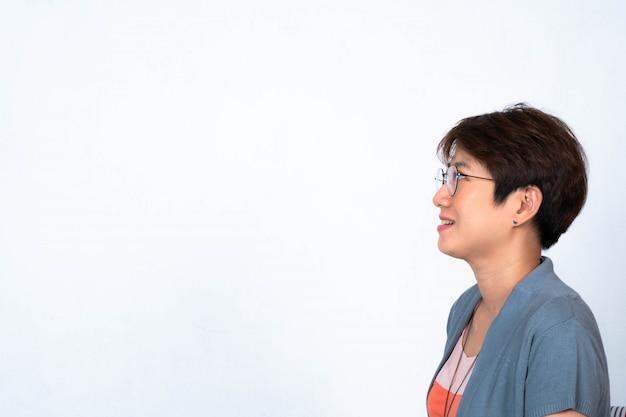 Portrait de femme asiatique aux cheveux courts souriant porter des lunettes pour tourner le côté.