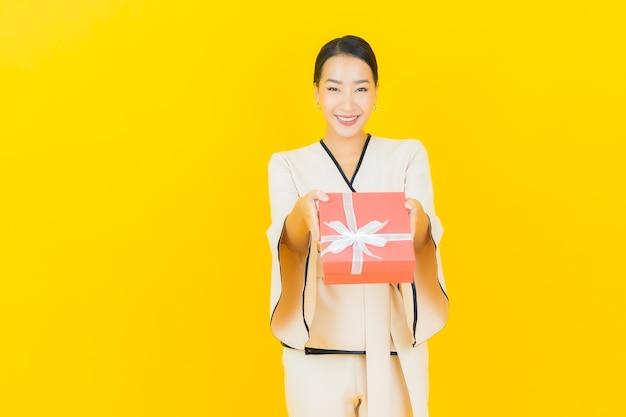 Portrait de femme asiatique belle jeune entreprise avec boîte-cadeau rouge sur mur jaune