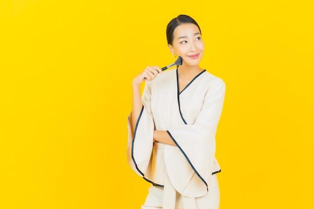 Portrait de femme asiatique belle jeune entreprise avec pinceau cosmétique maquillage sur mur jaune