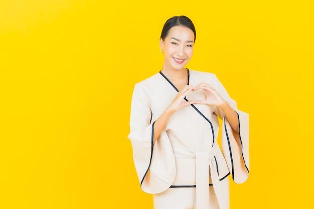 Portrait de femme asiatique belle jeune entreprise souriant avec costume blanc sur mur jaune