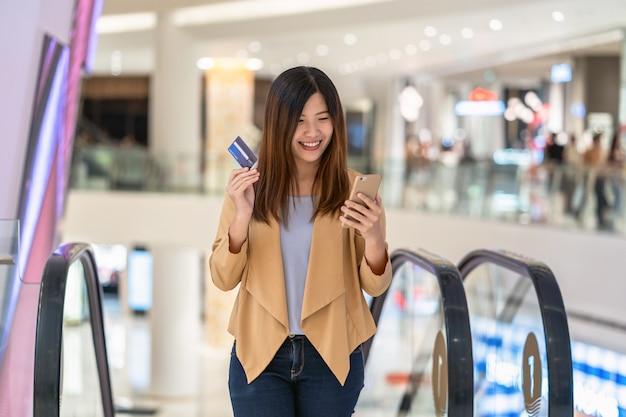Portrait de femme asiatique avec carte de crédit avec smartphone