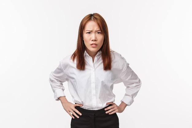 Portrait de femme asiatique déçue et stricte tenir la main sur la taille et se pencher en avant, froncer les sourcils avec blâme, accuser la personne d'être impoli, réprimander l'employé désobéissant sur le mur blanc