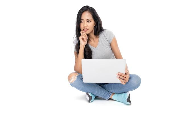 Portrait d'une femme asiatique est assise sur le sol. elle réfléchit en utilisant un ordinateur portable